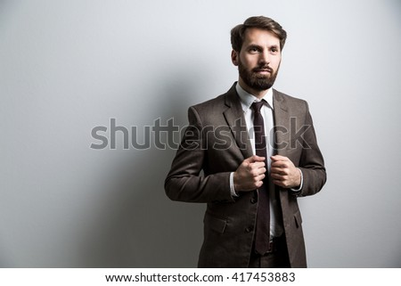 Businessperson in suit standing against light wall. Mock up - stock photo