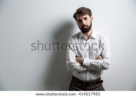 Businessperson in white shirt standing against blank wall with his arms crossed. Mock up - stock photo