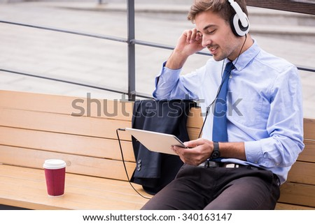 Businessperson listening music and waiting for somebody - stock photo