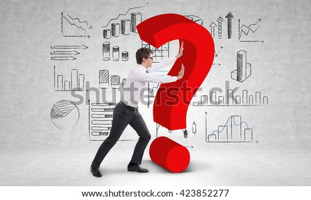 Businessperson pushing question mark in room with business charts on wall - stock photo