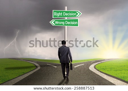 Businessperson with briefcase walking on the road and get two choices of the right decision or wrong decision - stock photo