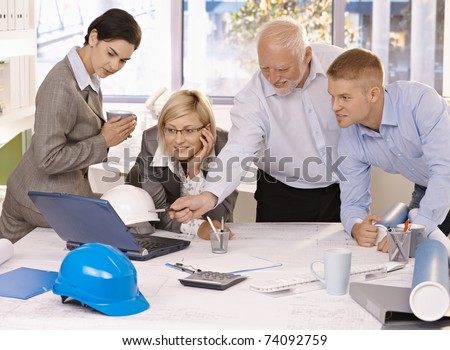 Businessteam discussing designer work on laptop computer, experienced architect pointing at screen.? - stock photo