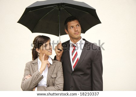 Businessteam of man and woman with umbrella - stock photo