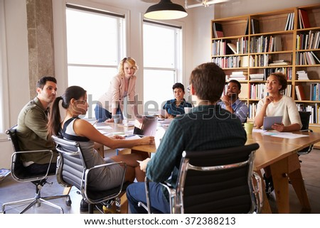 Businesswoman Addressing Team Meeting Around Table - stock photo
