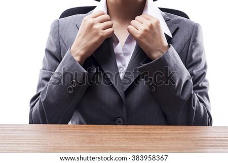 Businesswoman adjusting her collar at desk. - stock photo