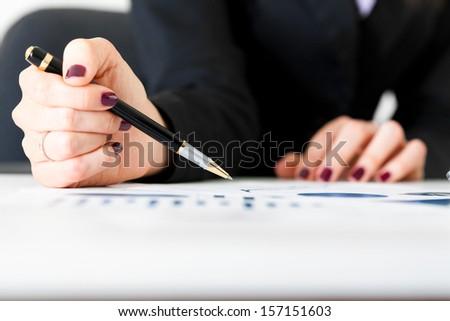 Businesswoman analyzing business charts - stock photo