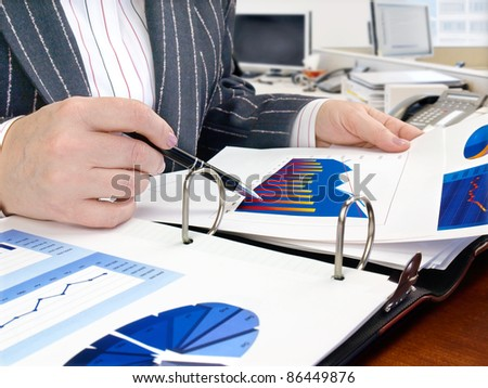 Businesswoman analyzing investment charts at his workplace - stock photo