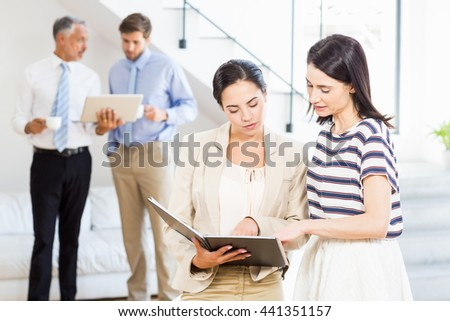 Businesswoman and a colleague looking at diary while businessmen discussing in the background - stock photo