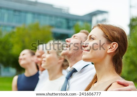 Businesswoman and business team outdoors looking in one direction - stock photo