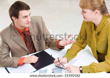 Businesswoman and businessman discuss a plan at meeting - stock photo