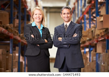 Businesswoman And Businessman In Distribution Warehouse - stock photo