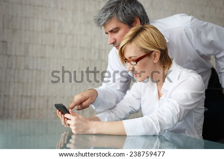Businesswoman and businessman in office watching financial data on tablet - stock photo