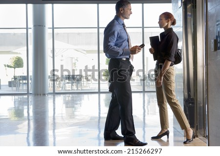 Businesswoman and businessman standing beside elevator in lobby, face to face, talking, profile - stock photo
