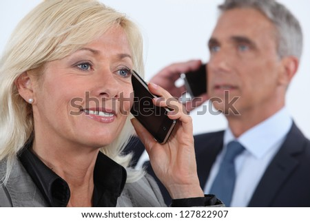 businesswoman and businessman talking on their cells - stock photo