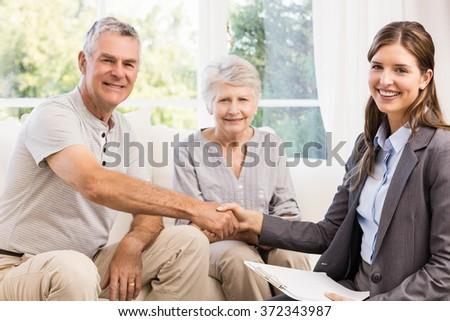 Businesswoman and senior man handshaking at home - stock photo