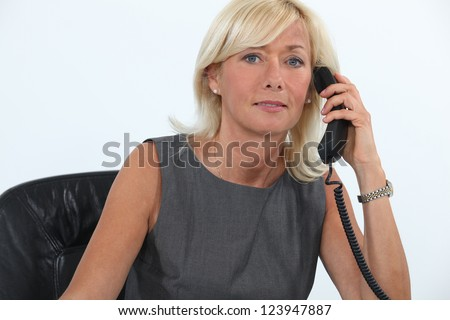 Businesswoman answering the telephone - stock photo