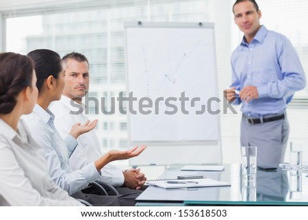 Businesswoman asking question during presentation in bright office - stock photo