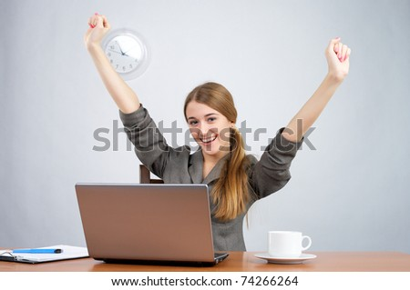 Businesswoman at desk with arms thrown up, while looking at camera - stock photo