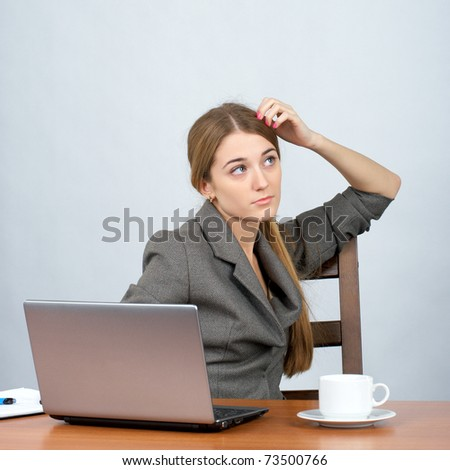 Businesswoman at desk with hand on head, looking into distance - stock photo
