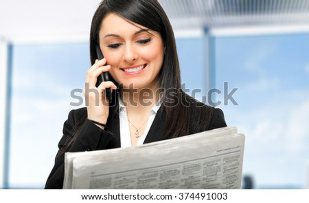 Businesswoman at the phone in her office - stock photo