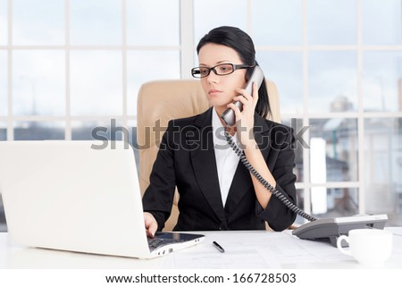 Businesswoman at work. Confident young business woman talking on the phone and using computer while sitting at her working place - stock photo