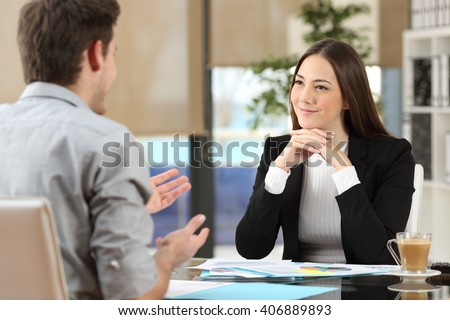 Businesswoman attending listening to a client who is talking at office - stock photo