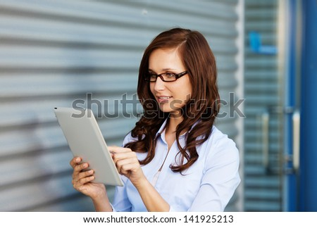 Businesswoman browsing the internet using her tablet - stock photo
