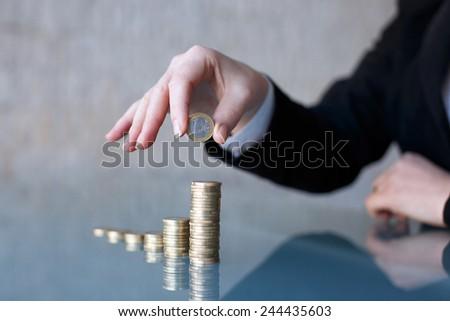 Businesswoman building growing one euro columns, saving money concept, closeup - stock photo