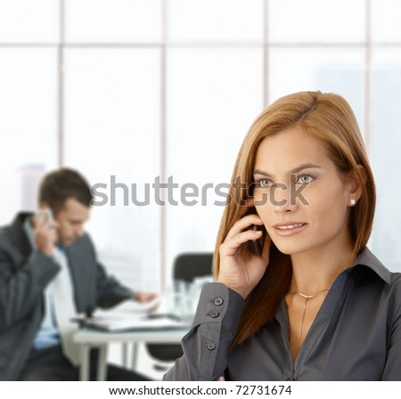 Businesswoman busy taking phone call in office, coworker working at meeting table.? - stock photo