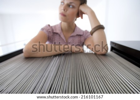 Businesswoman by filing cabinet - stock photo