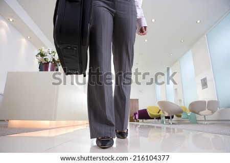 Businesswoman by reception, low section - stock photo