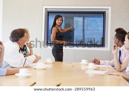 Businesswoman By Screen Addressing Boardroom Meeting - stock photo