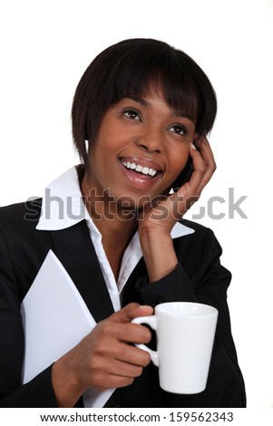 Businesswoman chatting on the phone with a hot drink - stock photo