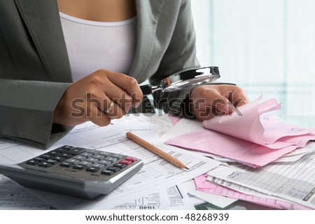Businesswoman checking bills using magnifying glass in the office - stock photo