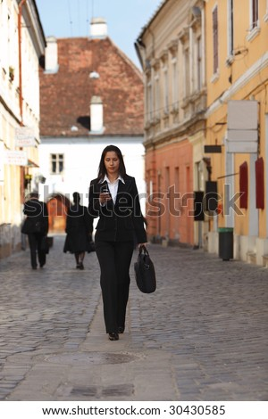 Businesswoman checking her mobile while walking. - stock photo