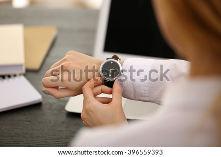 Businesswoman checking the time on her wrist watch, close up - stock photo