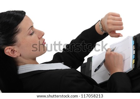 Businesswoman checking time on her watch - stock photo