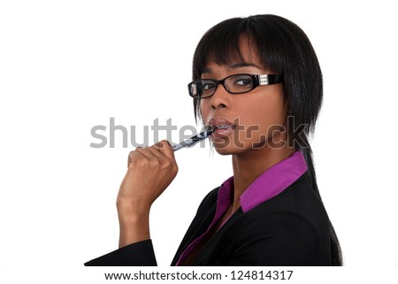 Businesswoman chewing on her pen - stock photo