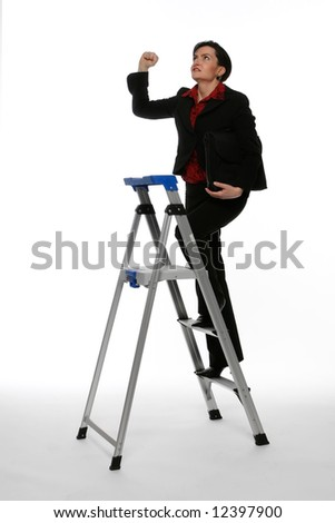 Businesswoman climbing a stepladder with a determined expression on her face shaking her fist at the ceiling - stock photo