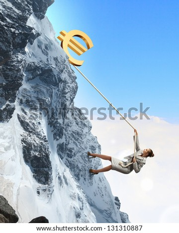 businesswoman climbing mountain with euro on top - stock photo