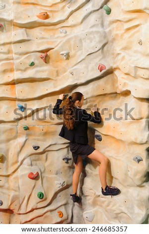 Businesswoman climbing on man-made cliff in the sport centre - stock photo