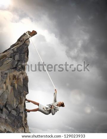 businesswoman climbing steep mountain hanging on rope - stock photo