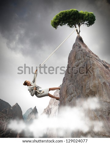 businesswoman climbing steep mountain with tree on top hanging on rope - stock photo