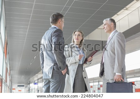 Businesswoman communicating with male colleagues on train platform - stock photo