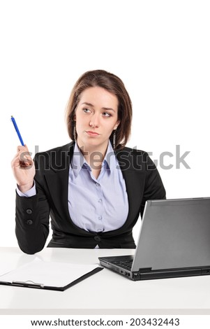Businesswoman contemplating seated at a desk isolated on white background - stock photo