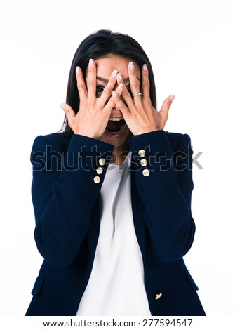 Businesswoman covering her eyes with hands and looking at camera through fingers. Isolated on a white background - stock photo