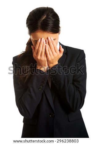 Businesswoman covering her face because of shame. - stock photo