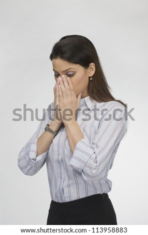 Businesswoman covering her face with her hands - stock photo