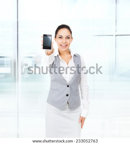 businesswoman displaying mobile cell phone, business woman show touch screen in modern office - stock photo