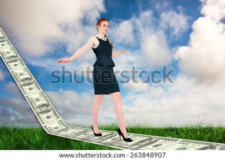 Businesswoman doing a balancing act against green grass under blue sky - stock photo